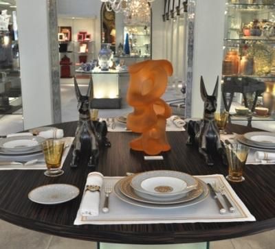 Cascade, Pollitt's orangesicle-colored glass sculpture gracing the center of a dining table set with fine chine, crystal and silver placesettings inside Thomas Goode, London
