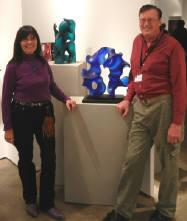 Harry Pollitt, glass artist, and his wife Gaye, at SOFA Chicago 2011, standing near two of his glass sculptures on exhibit.