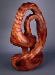 Finished redwood burl sculpture, entitled Infinity Rising, by Harry Pollitt.  Sweeping curves, large amounts of negative space and a lustrous finish are the key features of this piece.