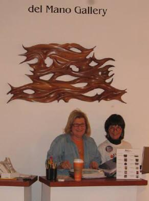 Jan Peters, Partner, del Mano Gallery, and Gaye, my love and wife, setting up the exhibit with Wave Length, my sculpted wall sculpture, displayed behind the gallery desk.
