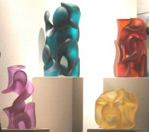 Four contemporary glass sculptures created with sweeping lines, curves and negative space by Harry Pollit, glass artist.  In luminous color, they are hyacinth, jade green, orange red and citrine.