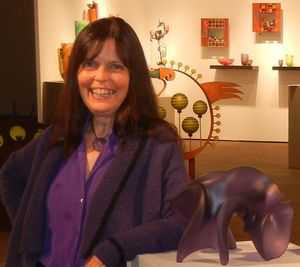 Gaye at SOFA Chicago 2013 standing near four Pollitt glass sculptures