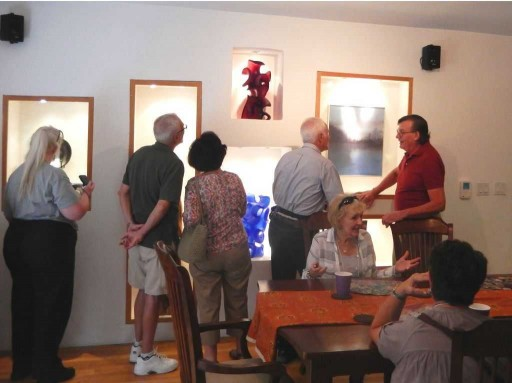 Visitors viewing two of Pollitt's glass sculptures and seated enjoying lunch.