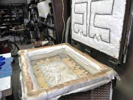 Plaster mold for Pollitt's glass wall sculpture placed in the kiln