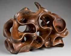 Sitting horizontally is Morph II, completed Windshake Walnut wood sculpture, revealing sweeps, curves and dynamic penetrations.