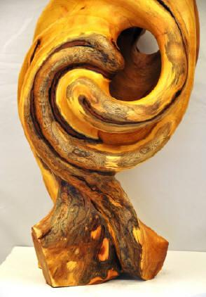 Even after complete sculpting the central section of this full-trunk osage orange wood sculpture remains gloriously contorted.