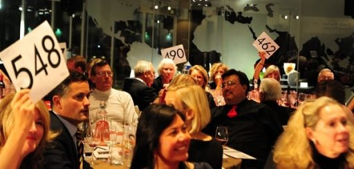 Large group of dinner attendees holding up their bid cards for auctioneer to see during MOG Red Hot Auction