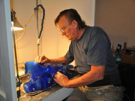 Pollitt cold working his new, blue glass sculpture using fine-mist water spray and diamond sandpaper.