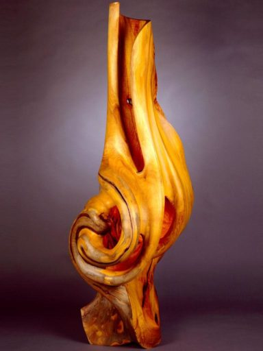 Monumental size osage orange wood sculpture named Charybdis by Harry Pollitt stands tall and glorious in deep tones of gold and brown.