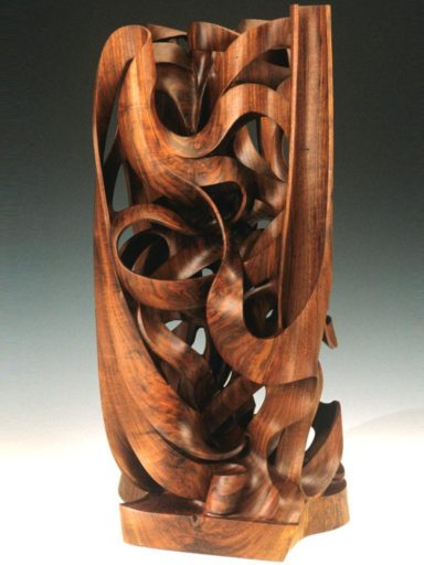 Sweep, curves, organic movement in wood.  A monumental wood sculpture called Gaia.