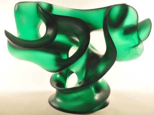 T with 'Tude, emerald green cast glass shaped abstractly like the letter 'T,' is proclaimed by the artist to be a glass sculpture with attitude.