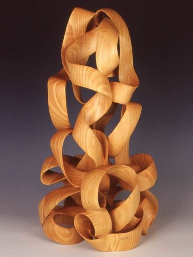 Up Draft, sculpture in wood by Harry Pollitt looking very much like a pile of ribbons being blown upward by a draft of air.