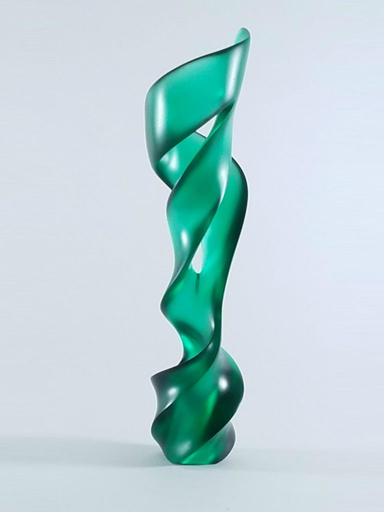 A medium polish finish on the Pollitt glass sculpture, called Green Piece, reveals shadows and lines from its far side.